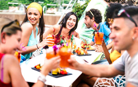 Happy friends drinking cocktails at pool party - Young people having fun in luxury resort restaurant - Vacation lifestyle concept with guys and girls enjoying drinks and fruit - Focus on central woman