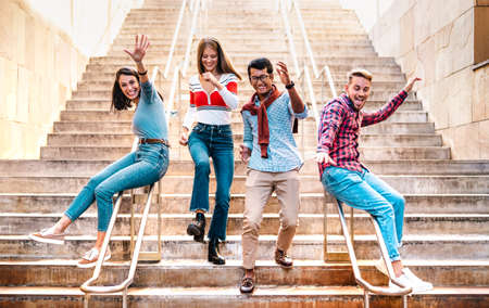 Multiethnic friends walking down stairs with stupid funny moves - Happy guys and girls having fun at urban city center on party mood - College students in travel holidays  - Bright warm filter