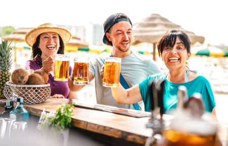 Mixed age friends toasting beer at chiringuito beach bar - Friendship life style concept with happy people enjoying time together on summer festival