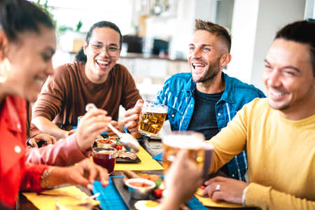Young people drinking beer and juices at brunch meal - Friendship life style concept with young milenial people enjoying happy hour time together at penthouse terrace pub - Warm bright vivid filter 스톡 콘텐츠