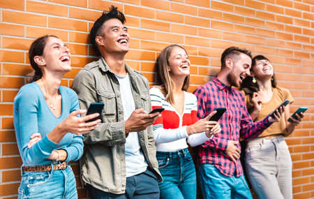 Multicultural friends laughing using smartphone at wall on university college campus - Young people addicted by mobile smart phones - Technology concept with always connected milenials - Vivid filter