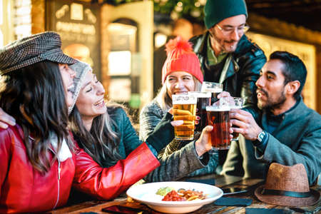 Happy multicultural friends drinking beer with nachos outdoors at night - Food and beverage lifestyle concept on young people enjoying time together outside