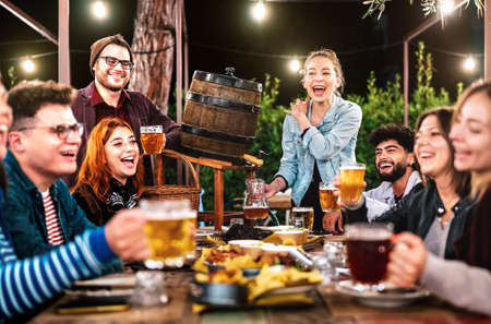 Happy men and women having fun drinking out at beer garden - Social gathering life style concept on young people enjoying hangout time together at night - Warm filter with shallow depth of field 스톡 콘텐츠