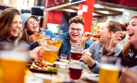 Happy friends drinking beer with mixed food at indoor venue - Social gathering life style concept on young people enjoying hangout time eating together - Vivid filter with shallow depth of field