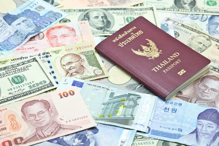 Thailand passport on mixed currency banknotes