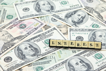 Word interest on pile of US dollar banknotes