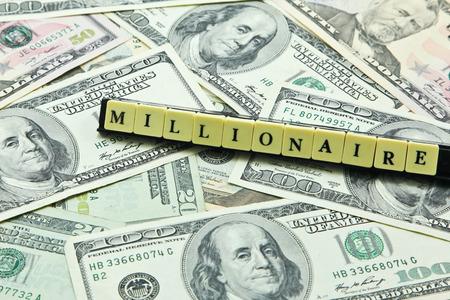 millonario: Millonario Palabra en la pila de billetes de d�lar