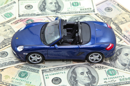 Sport car model on pile of US dollar banknotes Archivio Fotografico