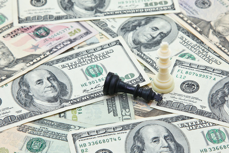 Chess kings on pile of US dollar banknotes