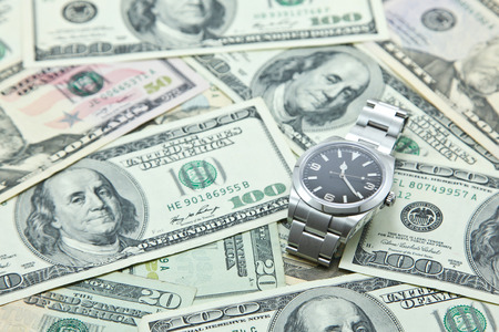 Swiss watch on pile of US dollar banknotes