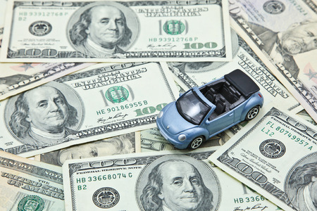 Car model on pile of US dollar banknotes