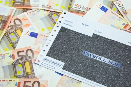 Payroll slip on pile of 50 Euro banknotes Archivio Fotografico