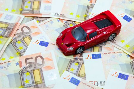 Red super car model on pile of 50 Euro banknotes Archivio Fotografico