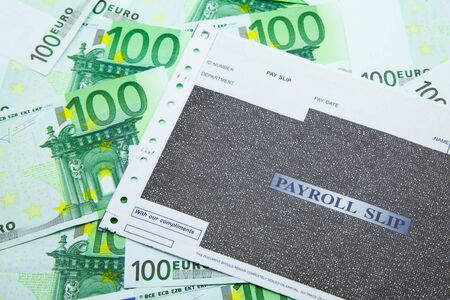 Payroll slip on pile of 100 Euro banknotes Archivio Fotografico