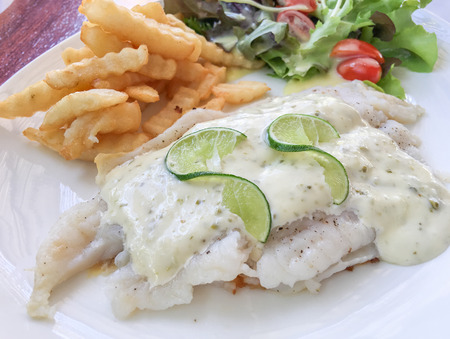 dolly: Dolly fish steak, french fries, tomato and salad on white plate. Stock Photo
