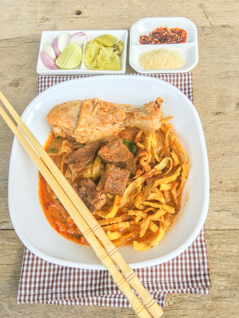 soi: Northern Thai Noodle Curry Soup with chicken, beef, pickles, onions, sugar, lemon and chili on wood table Thailand call Khao Soi Stock Photo