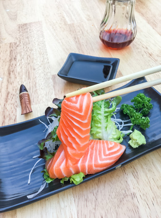 black grip: Hand grip chopsticks sashimi salmon with vegetable and radish in black plate on wooden table.