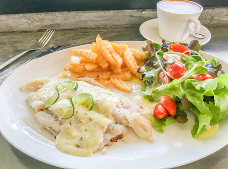 dolly: Dolly fish steak, french fries, tomato and salad on white plate and hot coffee.