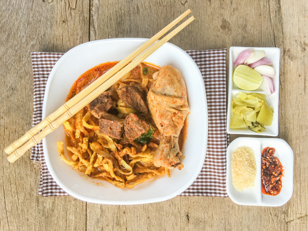 soi: Northern Thai Noodle Curry Soup with chicken, beef, pickles, onions, sugar, lemon and chili on wood table Thailand call Khao Soi. top view.