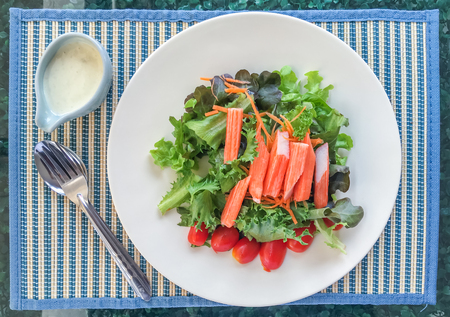 butter head: Salad contains green oak, red oak, butter head, tomato, green coral, carrot and Imitation crab stick with cream dressing at restaurant. top view.