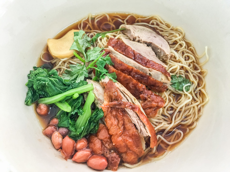 Roasted duck noodle with vegetable, ginger and peanut in restaurant. top view.