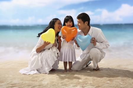 Family of three holding heart shape balloon at beach photo