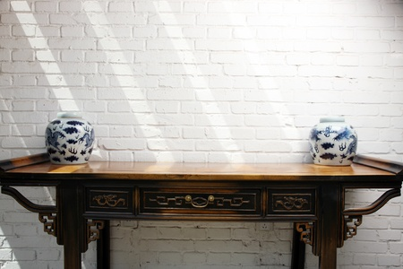 Traditional Chinese vase on a wooden table against a white wall Standard-Bild
