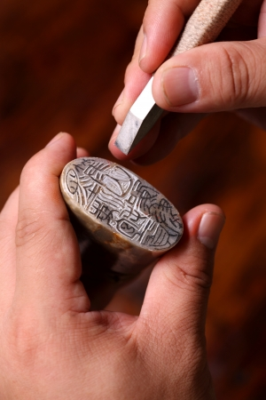 knack: Chinese craftsman carving a stone seal Editorial