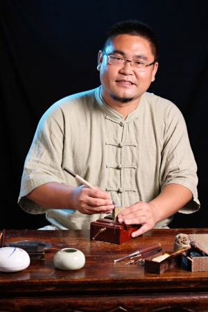 Chinese craftsman carving a stone seal photo
