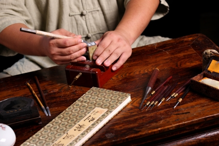 made in china: Chinese craftsman carving a stone seal Stock Photo