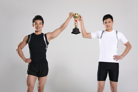 Young male athletes holding trophy smiling