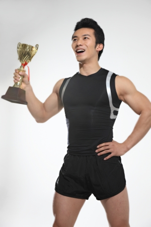 Male athlete holding up trophy  photo