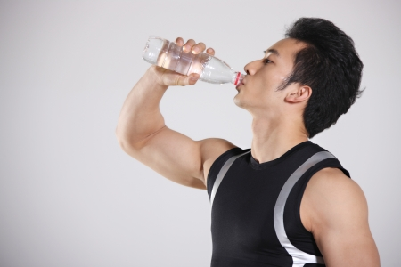 holding the head: The young athlete holdinig a bottle of water
