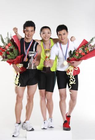 Gruppe von jungen Athleten halten Trophäe und Blumen