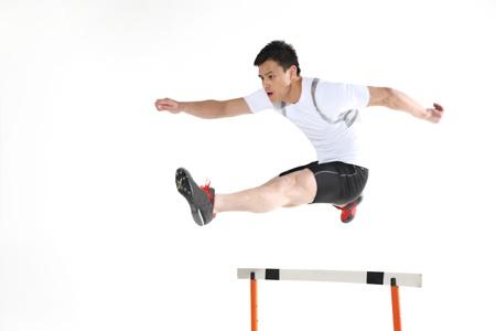 well build: Man jumping hurdle  Stock Photo