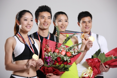 Group of young athletes holding trophy and flowers