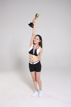 One young women holding trophy wearing medals  photo