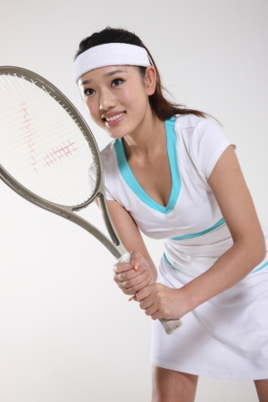chinese adult: Young woman playing tennis