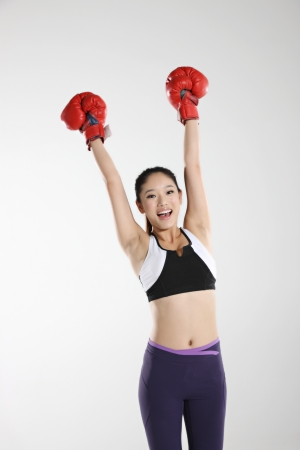 cut the competition: Young woman wearing boxing gloves
