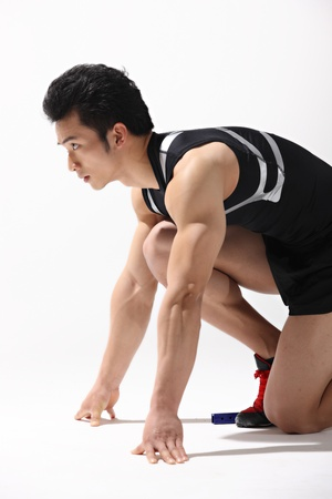 Male runner in starting blocks, close-up photo