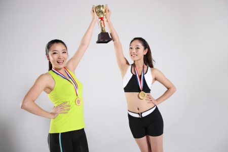 Two young women holding trophy wearing medals photo