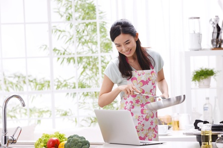 Young woman in kitchen cooking with reference the laptop photo