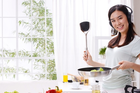 stereotypical housewife: Young woman in kitchen Stock Photo