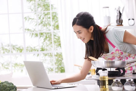 looking away: Young woman in kitchen cooking with reference the laptop Stock Photo