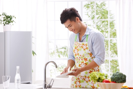 aprons: young man in kitchen Stock Photo