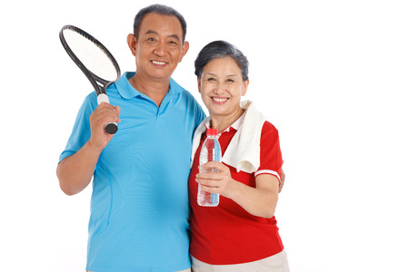 Old couple holding racket and water