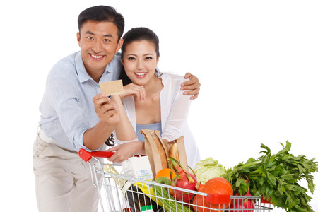 Young couple holding credit cart with vegetable photo