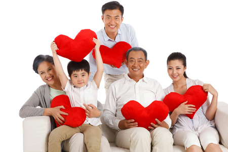 Whole family holding heart-shaped pillow