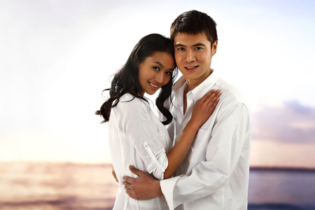 Young couple embracing on beach,smiling photo