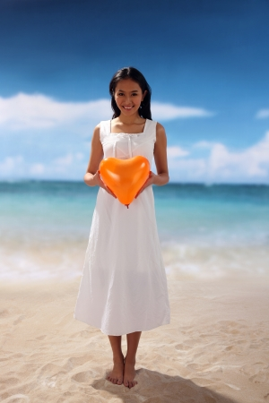 Young woman holding heart shape,smiling photo